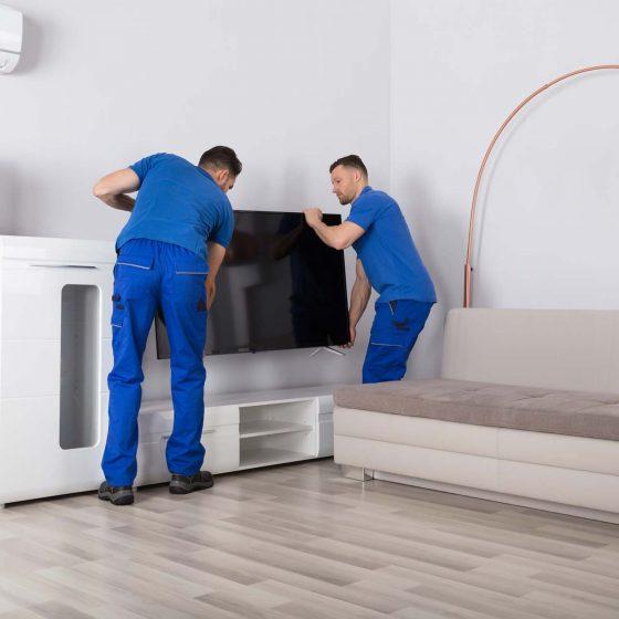 deux ouvriers plaçant la tv