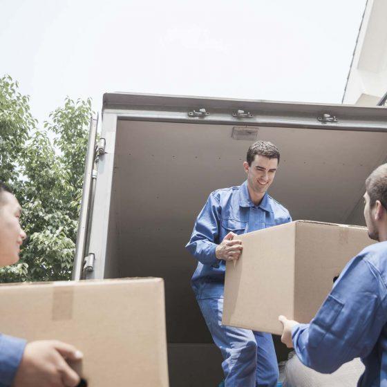3 ouvriers mettant les cartons dans le camion